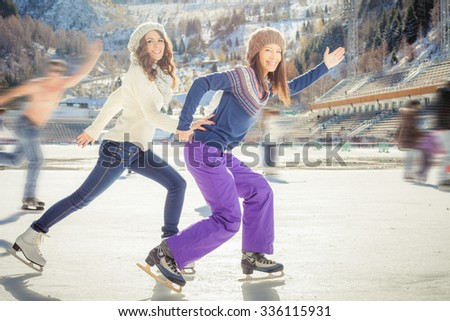 Image of group funny teenagers ice skating outdoor at ice rink, holding hands at Medeo stadium. Winter activities for a good mood and healthy mind. Action and speed - stock photo