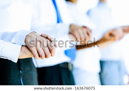 Image of group of businesspeople holding arms together. Teamwork - stock photo