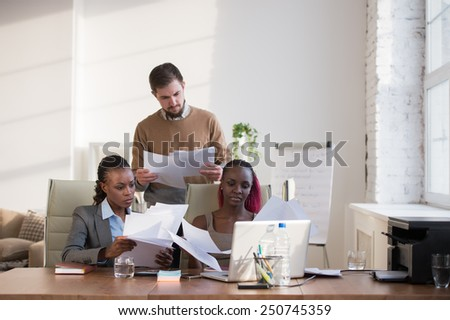 Image of group of three young business people of different ethnicity working together - stock photo