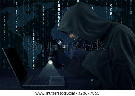 Image of hacker wearing balaclava and mask, stealing information on the laptop with flashlight and magnifying glass - stock photo