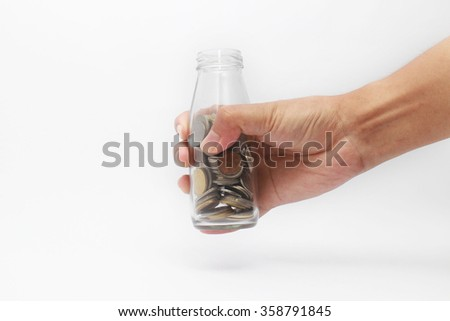 image of hand holding a bottle full of coins