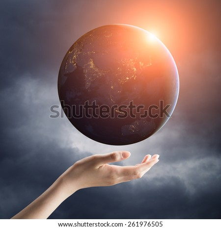 Image of hand holding earth planet on a palm with sun rays spreading around. Female hand is soft and calm. Elements of this image are furnished by NASA - stock photo