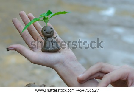 Image of hand holding the small plant growing on smile clay doll hand made model.Doll made from soil with sprout in garden nature background. save earth environment concept.selective focus. - stock photo