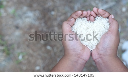 image of hand with rice in shape of love - stock photo