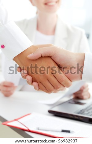 Image of handshaking of business partners with female on background - stock photo