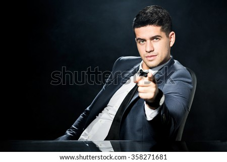 Image of handsome bossy man in black suit - stock photo