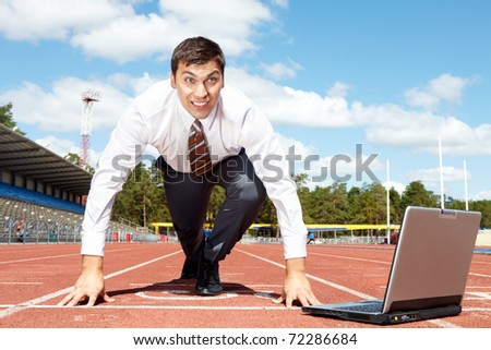 Image of handsome businessman getting ready for race at stadium - stock photo