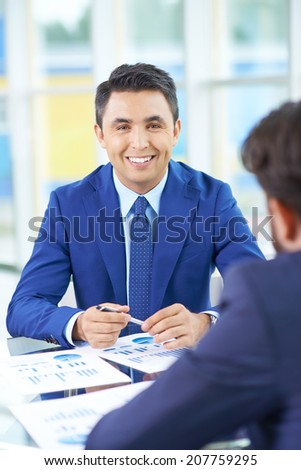 Image of handsome businessman looking at camera during communication with his colleague in office - stock photo