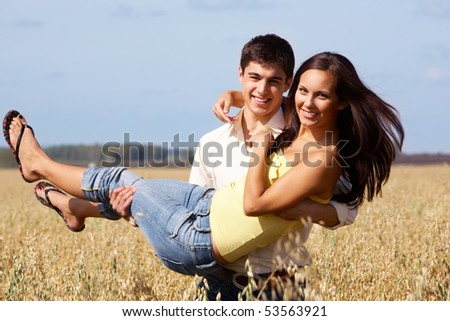 Image of handsome man holding beautiful girl while both looking at camera - stock photo