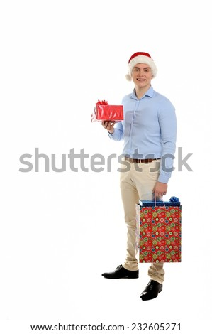 Image of handsome man in Santa cap carrying a bunch of gifts. Isolated on white background.