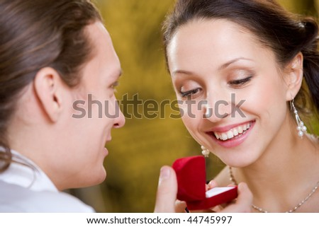 Image of handsome man making proposal to beautiful woman while holding small open box before her - stock photo