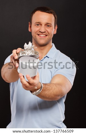 Image of handsome man with a gift in his hands