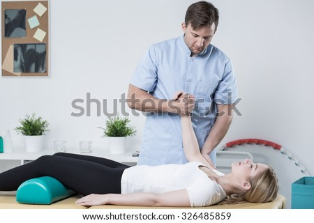 Image of handsome physiotherapist working with female patient - stock photo