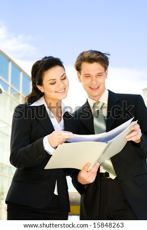 Image of happy businessman and businesswoman holding documents outside