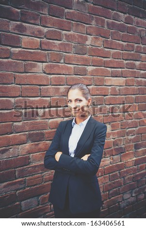 Image of happy businesswoman standing by brick wall and looking at camera   - stock photo
