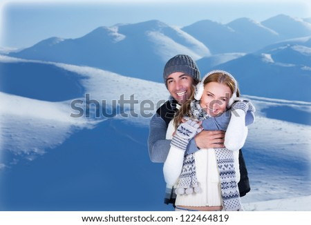 Image of happy couple hugging outdoors, young loving family having fun in snowy mountains, handsome man embracing his cute girlfriend, honeymoon in wintertime, winter holidays, love concept - stock photo