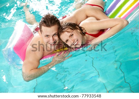 Image of happy couple looking at camera in swimming pool - stock photo