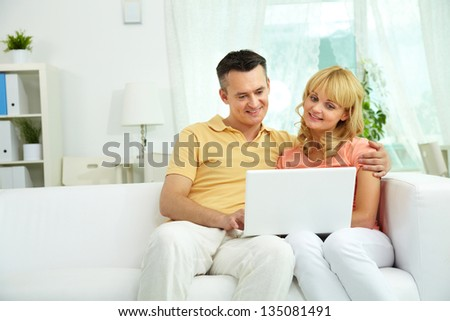 Image of happy couple sitting on the sofa and looking at laptop - stock photo