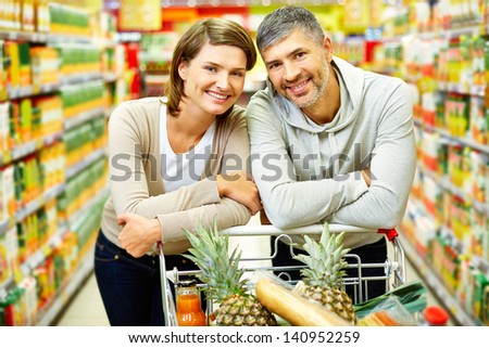 Image of happy couple with cart looking at camera in supermarket - stock photo