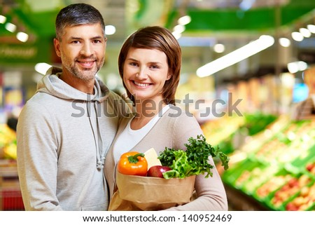Image of happy couple with healthy products looking at camera in supermarket - stock photo
