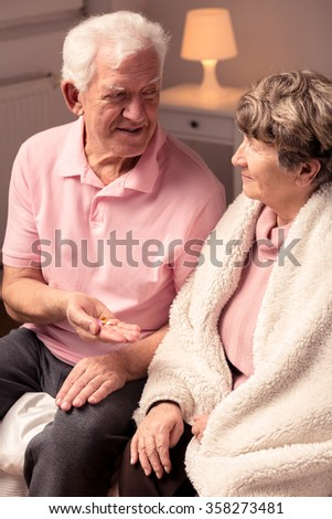 Image of happy elderly man holding pills in hand