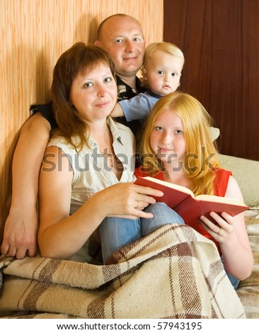 Image of happy family reading an interesting book together at home - stock photo