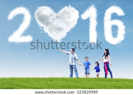 Image of happy family walking on the meadow with cloud shaped numbers 2016