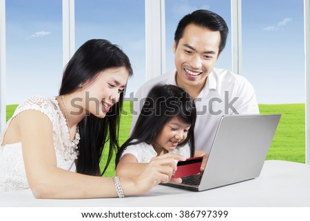 Image of happy family with two parents and their daughter buy online using laptop and credit card at home - stock photo