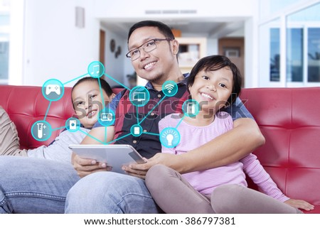 Image of happy father and his children holding digital tablet with smart house controllers system at home - stock photo