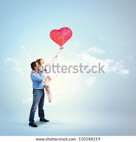 Image of happy father holding his daughter and a red heart baloon - stock photo