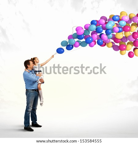 Image of happy father holding on hands daughter and balloons - stock photo