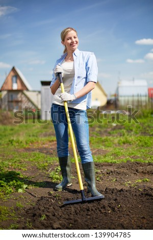 Image of happy female farmer looking at camera while working in the garden - stock photo