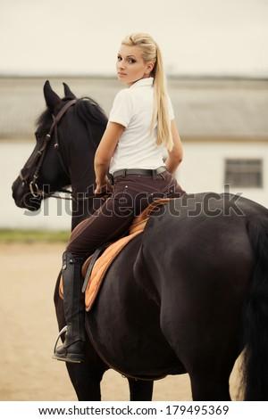 Image of happy female jockey on purebred horse outdoors - stock photo