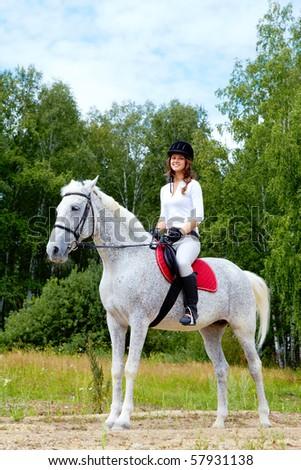Image of happy female jockey sitting on appaloosa horse outdoors - stock photo
