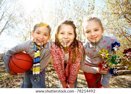 Image of happy friends with ball and toy looking at camera outdoors - stock photo