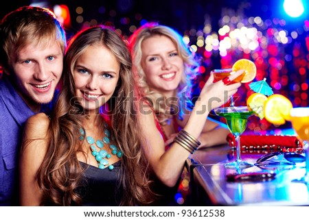 Image of happy girl looking at camera with her friends near by