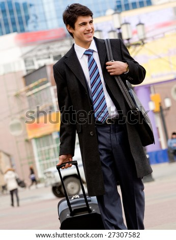 Image of happy guy in suit and coat walking with his baggage and bag - stock photo