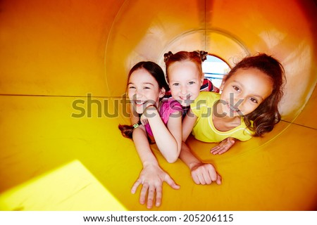 Image of happy little girls looking at camera while enjoying leisure - stock photo
