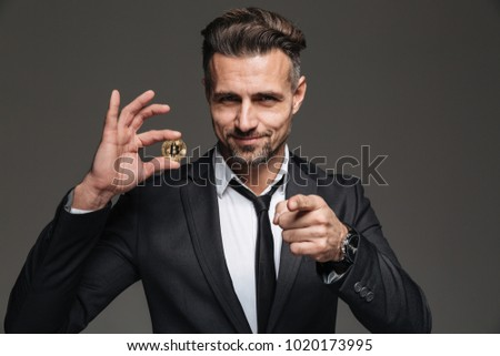 Image of happy male entrepreneur in business suit and tie holding crypto currency and pointing finger on camera isolated over dark gray wall