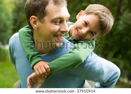 Image of happy man holding his son while having fun - stock photo