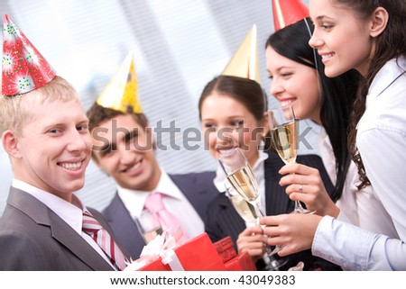 Image of happy man holding wrapped giftboxes with cheering friends on background - stock photo
