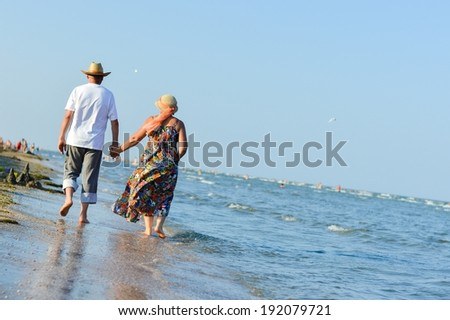 image of happy mature couple man & woman walking at seashore on sandy beach and embracing on summer sea outdoors background  - stock photo