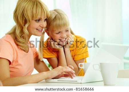 Image of happy mother and daughter using home internet