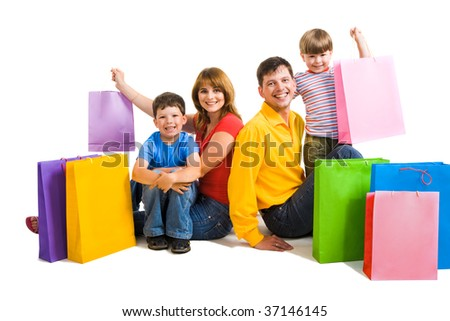 Image of happy parents and their two sons sitting in studio with shopping bags near by - stock photo