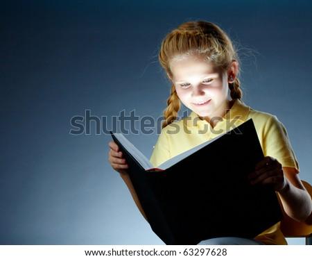 Image of happy schoolgirl reading interesting book - stock photo