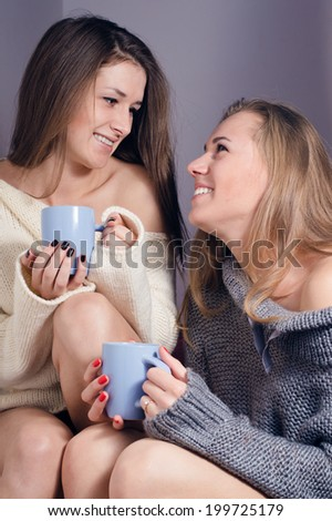image of 2 happy smiling pretty women sexy girlfriends drinking tea together wearing knitwear and looking at each other portrait