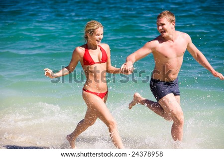 Image of happy teenage couple running by the seashore on summer day - stock photo