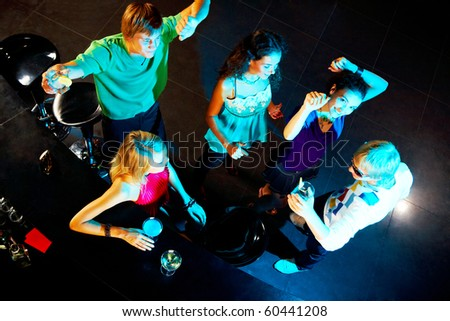 Image of happy teenagers dancing during party in the bar