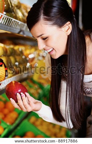 Image of happy woman with fresh apple in hand looking at it in supermarket - stock photo