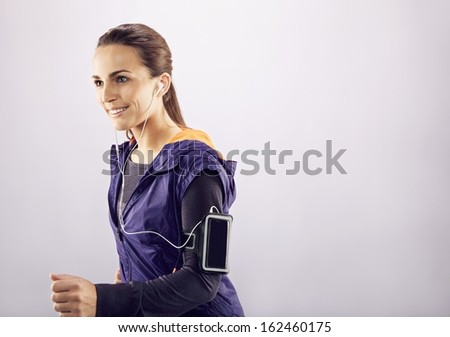 Image of happy young beautiful woman running and listening to music on grey background. Female runner running and smiling. - stock photo